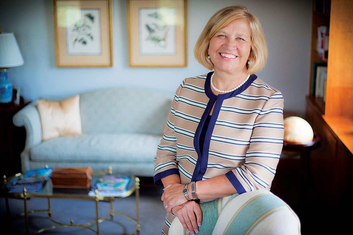 Nursing School dean Linda McCauley  stands next to a desk in a striped suit. A sofa is in the background with two nature prints on the wall above it.