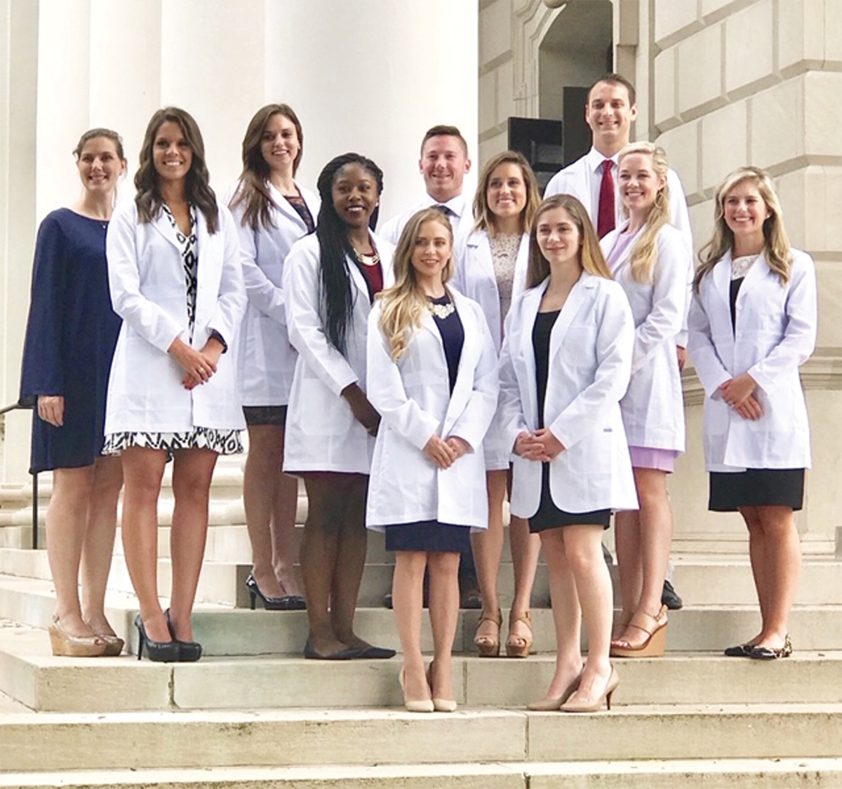 11 Nurse Anesthesia program students stand on the steps before a white marble building and columns. All but one are wearing white lab coats.