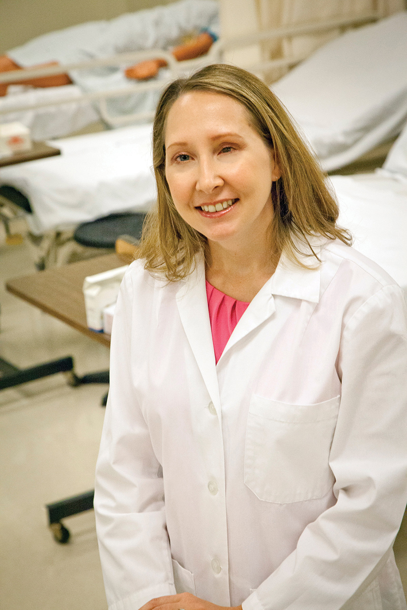 Melissa Owen wearing a white lab coat in a hospital setting.