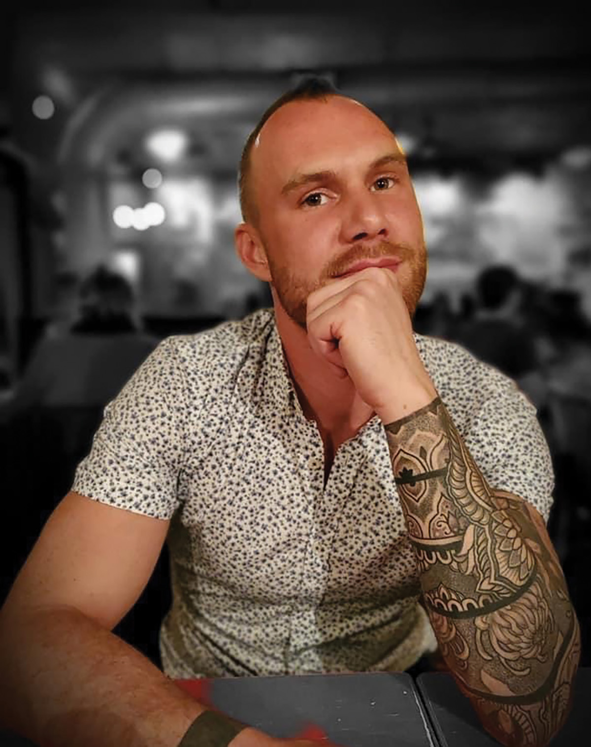 Devin P. Hussey sits at a table wearing a patterned shirt in an environmental portrait.